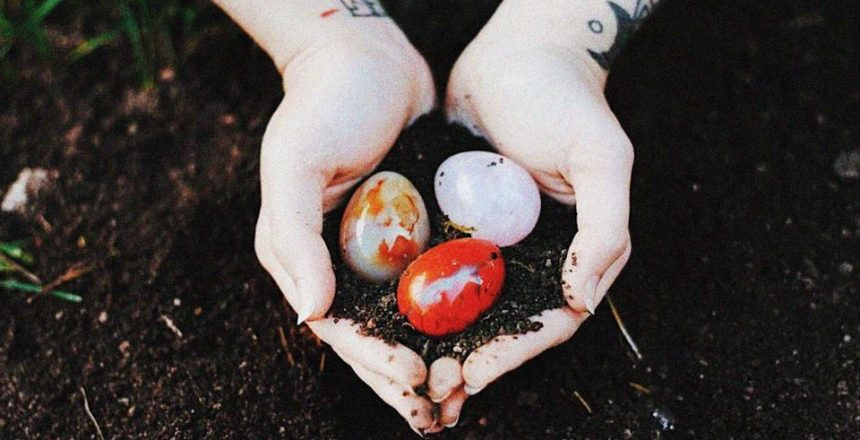Yoni eggs held in hands with earth